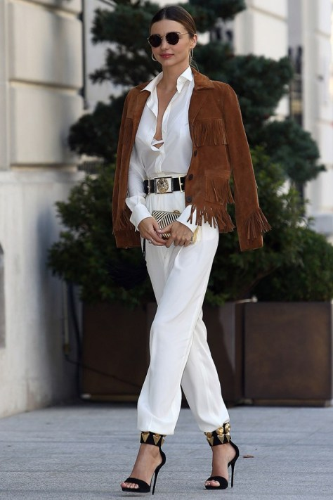 Miranda Kerr in an all white outfit with a brown suede fringed jacket
