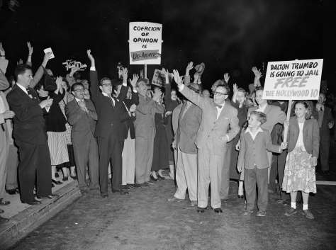 Screen writer Dalton Trumbo, center, right, waves to part of the crowd of 500 people who showed up at Los Angeles Airport, June 8, 1950, in a farewell demonstration before Trumbo left for Washington, where he and John H. Lawson will begin jail terms for contempt of Congress. At right are Trumbo's children, Nicola and Christopher, and his wife, Cleo. Trumbo refused to answer the House Un-American Activities Committee question of whether he is or ever was a communist. (AP Photo/Ed Widdis)